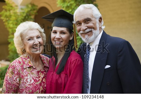Portrait of a young female graduate with grandparents smiling - stock photo