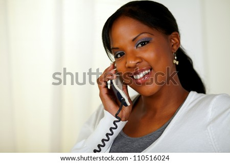 Portrait of a young female looking at you while talking on phone at soft colors composition