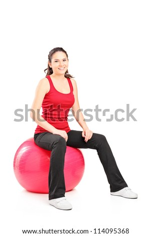 Portrait of a young female sitting on a pilates ball isolated on white background - stock photo