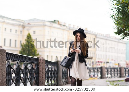 Portrait of a young female student reading message on mobile phone while goes from the university after lecture, stylish pretty hipster girl chatting on cell telephone during walking on the street  - stock photo