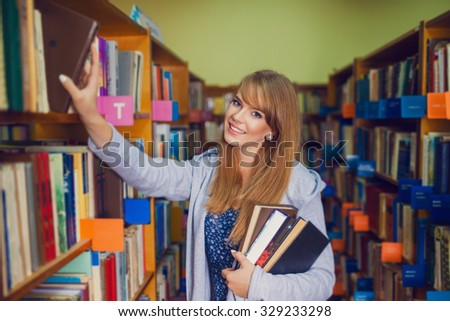 Portrait of a young female student standing in a university library