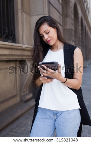 Portrait of a young female tourist using digital tablet computer for navigation while walking on the street in summer day, latin business woman working on touch pad while standing in urban setting - stock photo