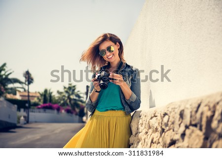 Portrait of a young, fit and attractive woman taking a photo outdoor. Posing on the street on a sunny summer day. Girl looking at the camera. - stock photo