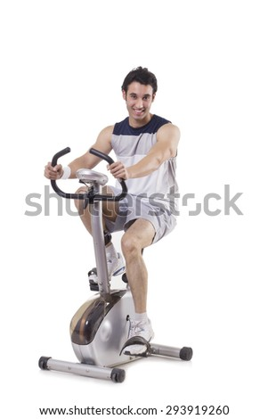 Portrait of a young fit man on exercise bike over white background - stock photo