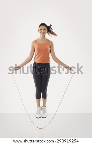 Portrait of a young fit woman skipping over white background - stock photo