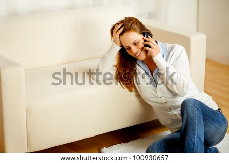Portrait of a young friendly woman having fun on mobile phone at home