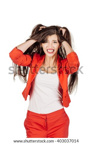 portrait of a young frustrated woman pulling out hair over white. human emotion expression and lifestyle concept. image on a white studio