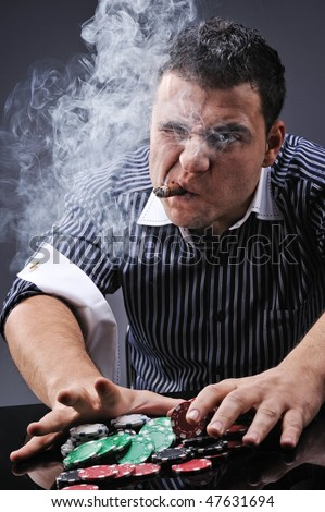 Portrait of a young gangster smoking and playing poker - stock photo