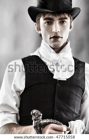 Portrait of a young gentlemen wearing dinner jacket and black top hat. Shot in a studio. - stock photo