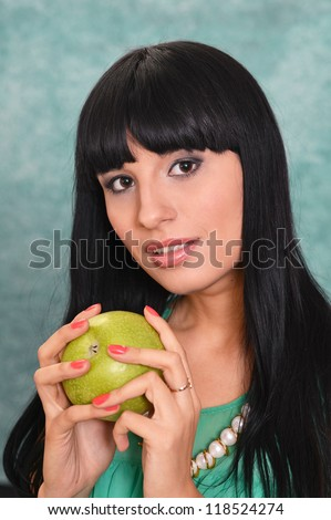 portrait of a young girl and apple on a green background - stock photo