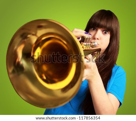 portrait of a young girl blowing trumpet on green background - stock photo