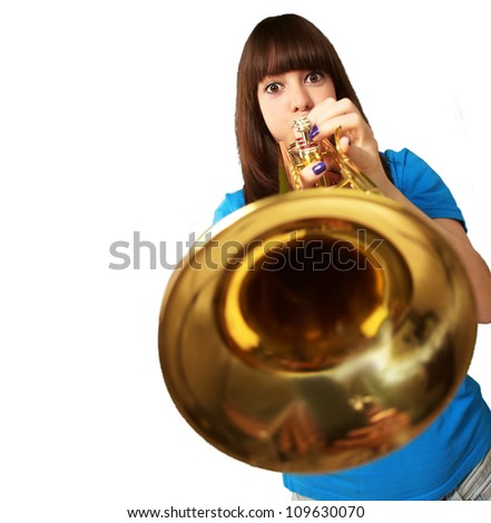 portrait of a young girl blowing trumpet on white background