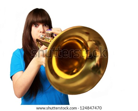 portrait of a young girl blowing trumpet on white background - stock photo
