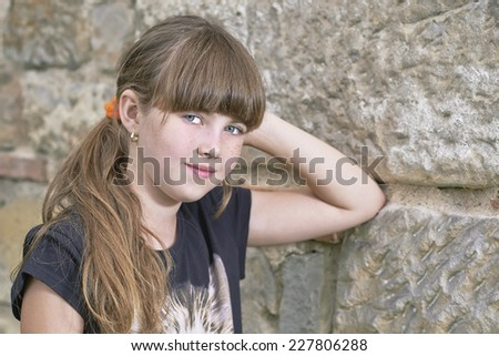 Portrait of a young girl by the stone wall