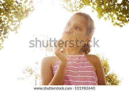 Portrait of a young girl eating an ice cream in the park, under golden light and trees. - stock photo