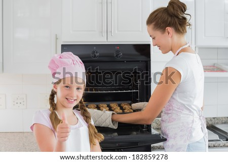 Portrait of a young girl gesturing thumbs up while mother removes cookies from the oven in the kitchen - stock photo
