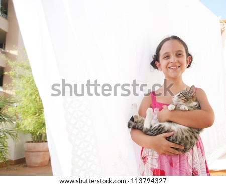 Portrait of a young girl holding a cat in her arms and smiling at the camera, while standing next to white linen hanging to dry on a terrace.