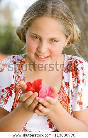 Portrait of a young girl holding hibiscus flowers in her hands and smiling. - stock photo