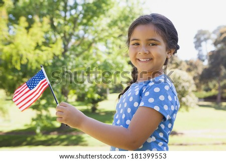 Portrait of a young girl holding the American flag at the park