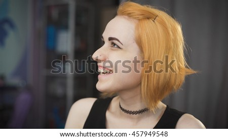 Portrait of a young girl in a beauty salon. The client waits for his master in the chair, her bob and red hair. - stock photo