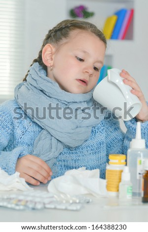 Portrait of a young girl in a blue sweater with pills at home