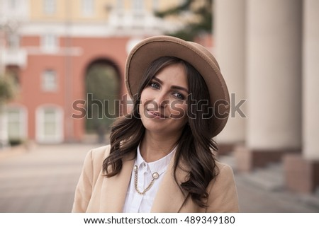 Portrait of a young girl in a hat and coat on a background of sepia columns