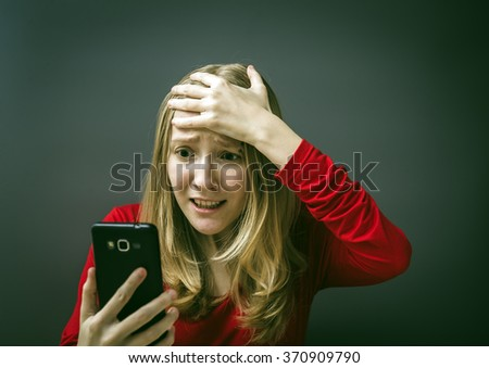 Portrait of a young girl in a red dress on a gray background. Bad news - stock photo