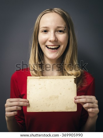 Portrait of a young girl in a red dress on a gray background. Woman holding a blank paper sheet with both hands - stock photo