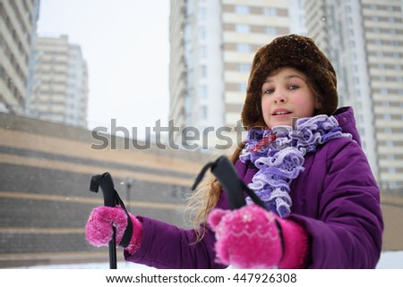 Portrait of a young girl in a winter hat with ski poles near the blocks of flats - stock photo