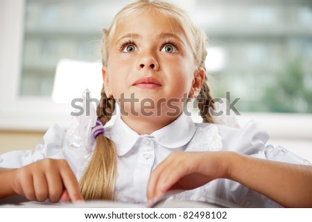 Portrait of a young girl in school at the desk. Horizontal Shot. She is very excited by book, daydreaming