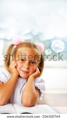 Portrait of a young girl in school at the desk. Vertical Shot. Daydreaming. Blank cloud with copyspace for your text and logo - stock photo