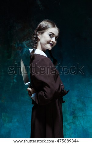 Portrait of a young girl in school uniform as killer woman