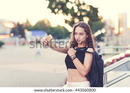 Portrait of a young girl in the city, makes selfie - stock photo