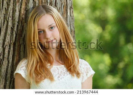 Portrait of a young girl leaning against a tree - stock photo