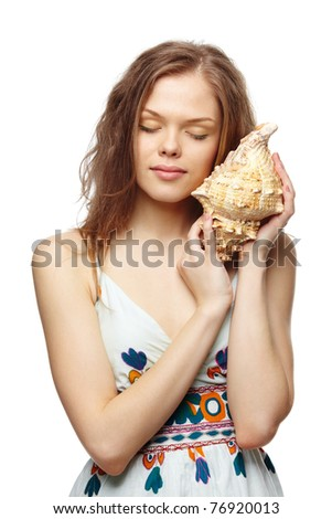 Portrait of a young girl listening to the seashell - stock photo