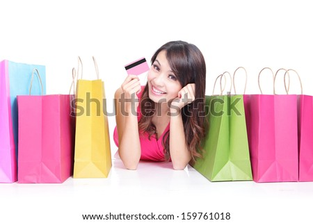 Portrait of a young girl lying with shopping bags and show credit card isolated on white , asian beauty - stock photo