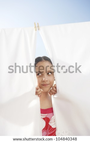 Portrait of a young girl peering through bed linen hung to dry in the sun on a clothes line, outdoors.