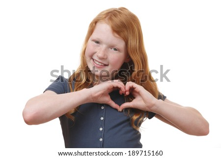 Portrait of a young girl showing heart shape with hands on white background - stock photo