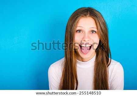 portrait of a young girl showing her tongue - stock photo