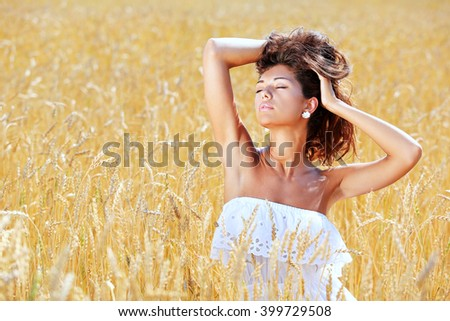 Portrait of a young girl sitting in a wheat field
