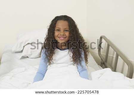 Portrait of a young girl sitting up in her hospital bed - stock photo