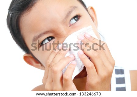 Portrait of a young  girl sneezing on a tissue paper. - stock photo