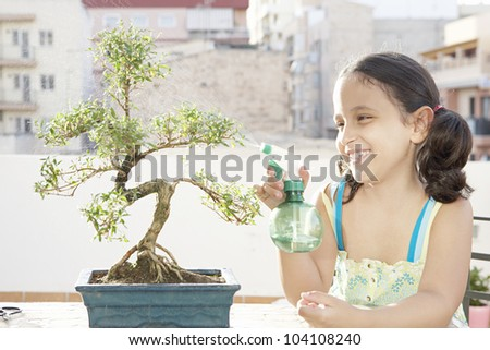 Portrait of a young girl watering a bonsai tree and smiling on a terrace.