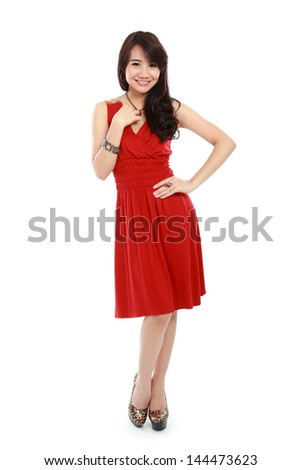 Portrait of a young girl wear red dress  in action and looking at camera