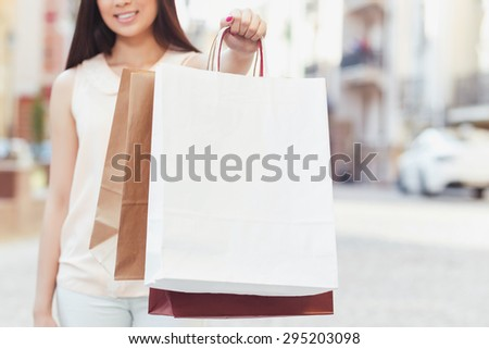 Portrait of a young girl wearing beige blouse and white jeans stretching her hand holding shopping bags in front of her, selective focus, beautiful old city on the background - stock photo