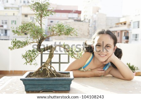 Portrait of a young girl with a bonsai tree in a busy city background, outdoors.