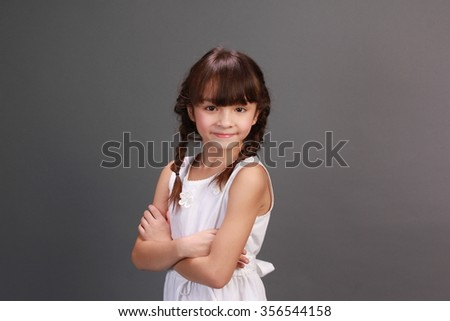 Portrait of a young girl with a grey background. She is looking at the camera and smiling. - stock photo