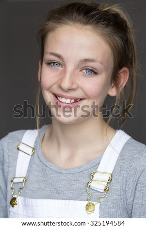 Portrait of a young girl with a grey background. She is wearing casual clothing and smiling at the camera. - stock photo