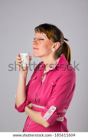 Portrait of a young girl with a paper cup of tea in hand on white background