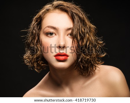 Portrait of a young girl with clean skin and red lips on a black background close-up. - stock photo